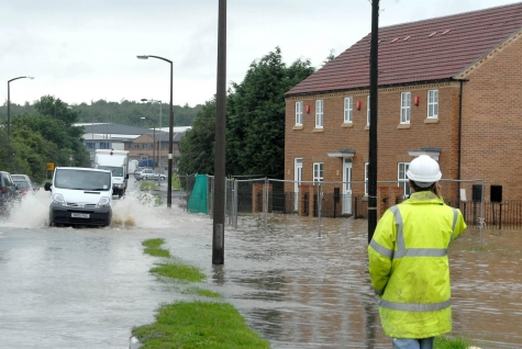 A person in a high-vis jacket standing next to a flooded road.