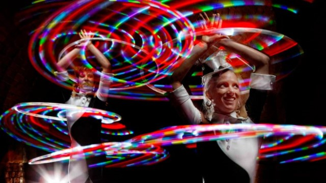 Halo perfomers dancing with illuminated hoops