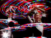 Two dancers performing, spinning illuminated hoops