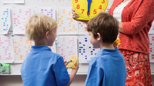Two boys at primary school learning about time with teacher and clock
