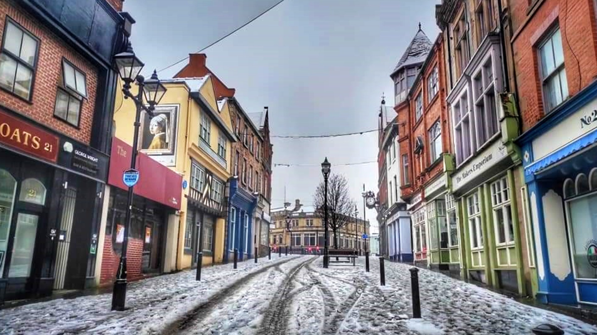 Rotherham High Street in the snow with shops on either side of the street